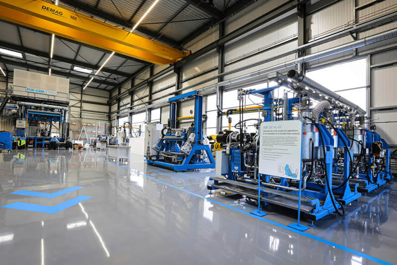 Better utilization and shorter distances within the approximately 1000 square meter hall. In the foreground: 6-component high-pressure metering machine with 40 ton mold carrier.